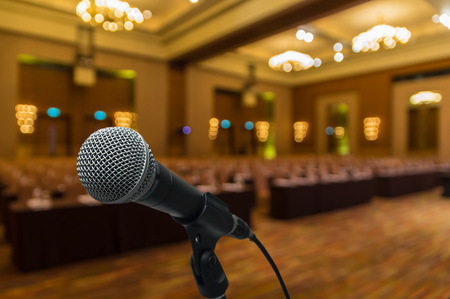 congress center: Microphone over the Abstract blurred photo of conference hall or seminar room background