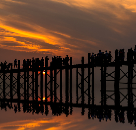 Sunset with silhouettes of many people on the U-Bein Bridge is the longest. in Amarapura ,Mandalay ,Myanmar Stock Photo