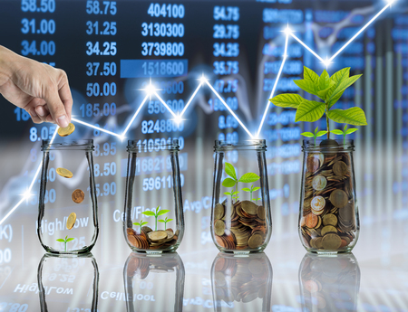 Hand putting Gold coins and seed in clear bottle on Stock market exchange data on LED display background, Business investment growth and trading concept