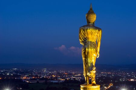 Buddha standing on a mountain at twilight time at Wat Phra That Khao Noi, Nan Province, Thailand, public domain