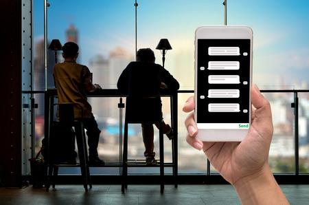 女性手で株式市場チャート、LED ディスプレイ上のクローズ アップ株式市場 exchange データの上の場所の前にチャット メッセージの順番を示す携帯電