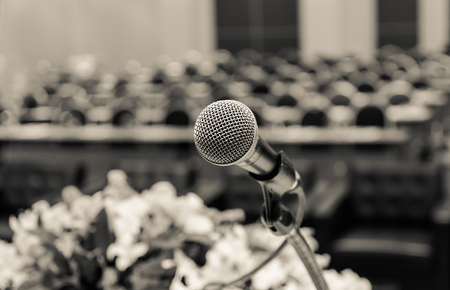 Microphone over the Abstract blurred photo of conference hall or seminar room background, vintage color tone Stock Photo