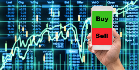 Female hand holding mobile phone touch screen showing buy and sell over the Stock market chart,Closeup Stock market exchange data on LED display, business trading concept