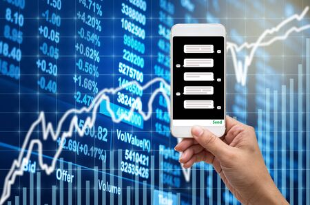 Female hand holding mobile phone showing the chat message before place the order over the Stock market chart,Closeup Stock market exchange data on LED display, business trading and technology concept