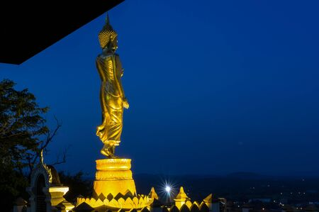 public domain: Buddha standing on a mountain at twilight time at Wat Phra That Khao Noi, Nan Province, Thailand, public domain