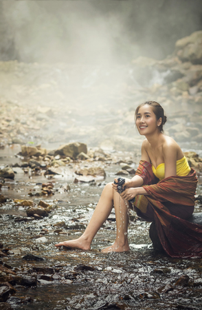 A beautiful Village women sitting and washing the clothes at the stream of waterfall or river, countryside and Folkways concept Stock Photo