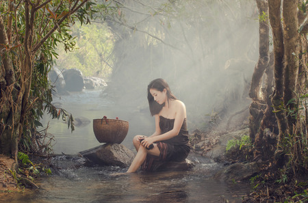folkways: A beautiful Village women sitting and washing the clothes at the stream of waterfall or river, countryside and Folkways concept Stock Photo