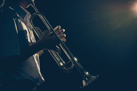 rehearse: Young student Musician playing the Trumpet with spot light and len flare over dark background on the stage, Musical concept