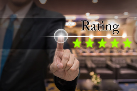 hotel reviews: Businessman pointing five star button to increase rating of hotel over Abstract blurred photo of conference hall or seminar room with attendee background, business evaluation concept, Increase rating Stock Photo