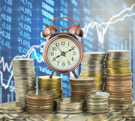 stacks of coins step thai baht with the vintage clock over the LED display Stock market exchange data background, Business investment and trading concept