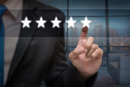 hotel reviews: Businessman pointing five star symbol to increase rating of company or hotel over blurred of interior lobby background, business evaluation concept, Increase rating