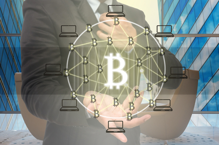 Block chain Text and Distributed computer network with Hand of businessman holding the icon over the Modern business building glass of skyscrapers,Distributed ledger technology and block chain concept