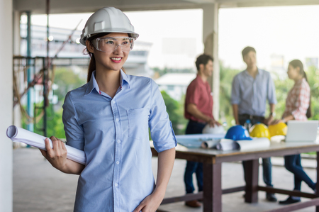 Portrait of Happy professional construction engineer woman holding the blueprint and wearing the safety helmet and glasses at the building site place background, industrial engineering concept Standard-Bild