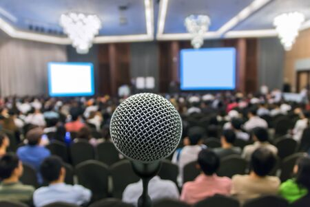 attendee: Microphone over the Abstract blurred photo of conference hall or seminar room with attendee background, Business meeting concept