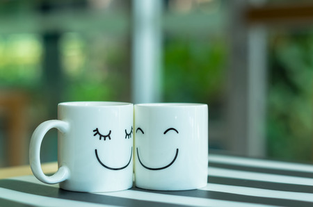 Two happy cups on the table, about love concept Stock Photo