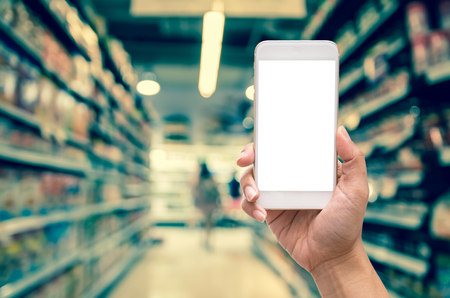 oncept: Female hand holding mobile smart phone on Supermarket blur background, business technology concept Stock Photo