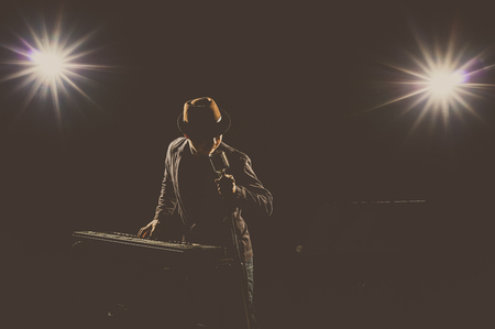 african sax: Musician playing a keyboard and singing a song on black background with spot light and lens flare, musical concept