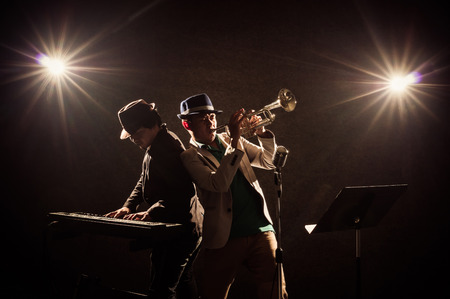 Musician Duo band playing a Trumpet and keyboard on black background with spot light and lens flare, musical concept
