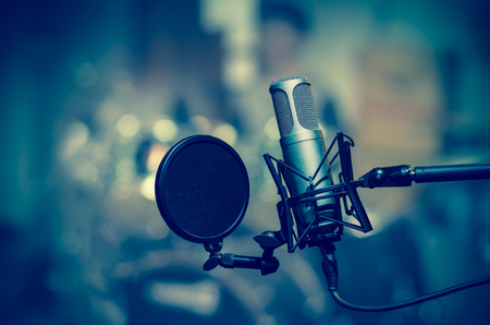 Professional condenser studio microphone over the musician blurred background, Musical instrument Concept Stock Photo