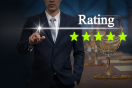 hotel reviews: Businessman pointing five star button to increase rating of hotel over workplace with Glass of water, paper and pencil on the table in the hall room, business evaluation concept, Increase rating