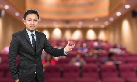Businessman with welcoming gesture on Abstract blurred photo of conference hall or seminar room with attendee background, business concept