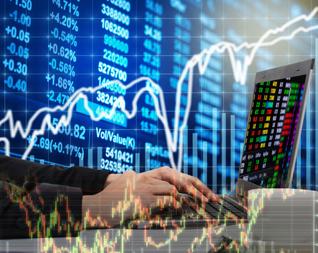 economic forecast: Businessman using the laptop working with Stock market chart in computer screen over the Stock market exchange on photo blurred of cityscape background, Business trading and technology concept