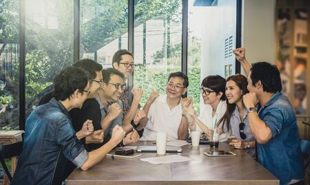 people in action: Group Of Asian Business people with casual suit working with happy action and celebrate in the Office or coffee shop, people business group concept Stock Photo