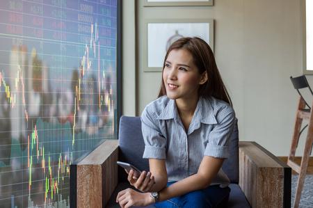 Happy asian geschäftsfrau sitzt auf Arbeitsraum und suchen die Börse Exchange Informationen und Trading-Grafik in der modernen Office, Business-Finanz-Konzept