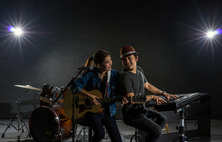 Musician duo band singing a song and playing music instrument with Fellow band musicians on black background with spot light and lens flare, musical concept