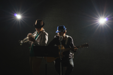african sax: Musician Duo band playing a Trumpet and singing a song and playing the guitar on black background with spot light and lens flare, musical concept