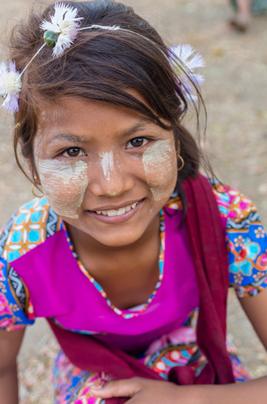 MANDALAY, MYANMAR - MARCH 12 : Unidentified Burmese girl with traditional thanaka on her face on March 12, 2016 in Mandalay, Myanmar.Thanaka is a yellowish-white cosmetic paste made from ground bark Editorial