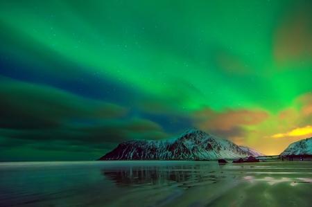 Aurora borealis over snowy islands from Uttakleiv beach of Lofoten, norway