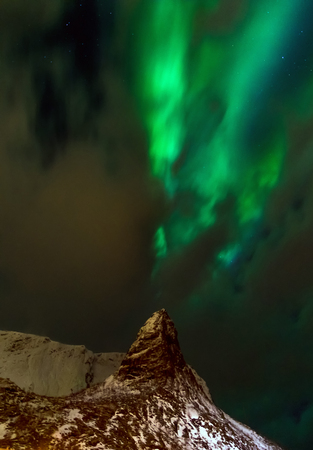 Aurora borealis over snowy islands from top view of Lofoten Stock Photo