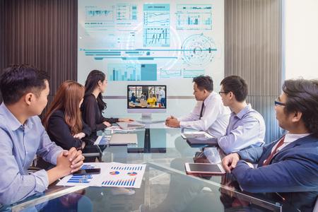 Groupe de l'équipe des affaires asiatiques ayant une vidéoconférence avec leur gestionnaire par l'affichage du moniteur dans la salle de conférence moderne, le concept de réunion des gens d'affaires