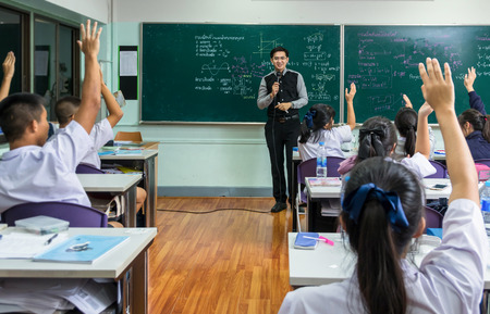 Asian teacher Giving Lesson over the the physics formular in thai laguage on black board in school classroom and students showing the hand for answer,school education concept,The teacher wrote himself 版權商用圖片