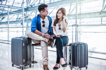 アジアのカップル旅行者のスマート フォンを使用して、飛行機を待機しているときに、歌を聞いて到着空港で荷物を持つ。恋人旅行と交通技術コン