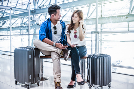 Asian couple traveler using smartphone and listening the song when waiting the airplane arrive with luggage at the airport. Lover travel and transportation with technology concept.