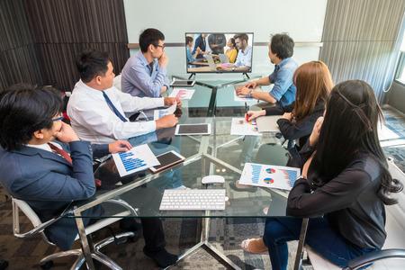Groupe d'entreprises asiatiques ayant une conférence vidéo avec leurs collègues d'un autre pays via un moniteur dans la salle de conférence moderne Banque d'images