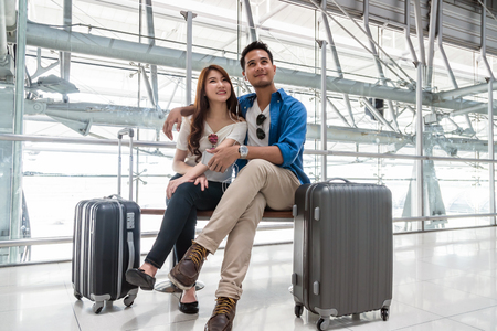 Asian couple traveler using smartphone and listening the song when waiting the airplane arrive with luggage at the airport. Lover travel and transportation with technology concept. Imagens - 81193745
