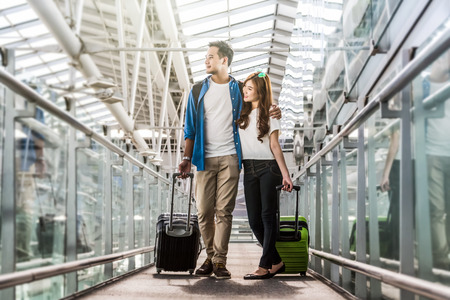 Asian couple traveler with suitcases at the airport. Lover travel and transportation with technology concept. 스톡 콘텐츠