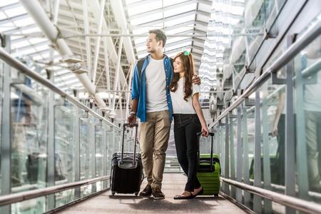 Voyageur de couple asiatique avec des valises à l & # 39 ; épaule de l & # 39 ; épaule et le transport avec le concept de la technologie Banque d'images - 81203653