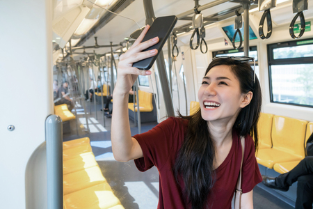 Asian woman passenger with casual suit taking selfie by the smart mobile phone in the BTS Skytrain rails or MRT subway for travel in the big city, lifestyle and transportation concept Imagens