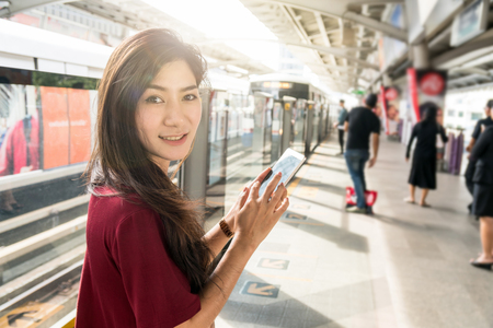 Asian woman passenger with casual suit using the technology tablet with lens flare in the BTS Skytrain rails or MRT subway for travel in the big city, lifestyle and transportation concept