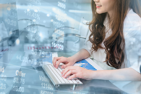 Closeup hand young asian business woman pressing the keyboard of computer over Stock market exchange data over store blur with bokeh background, people and trading business concept