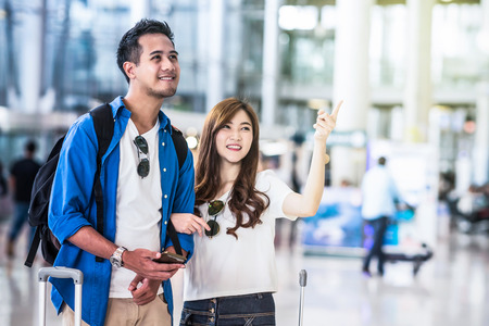 Asian couple traveler walking with suitcases in modern an airport, travel and transportation concept.motion style Banco de Imagens - 81203721