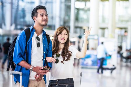 Aziatische paarreiziger die met koffers in modern een luchthaven, reis en vervoersconcept lopen Motiestijl