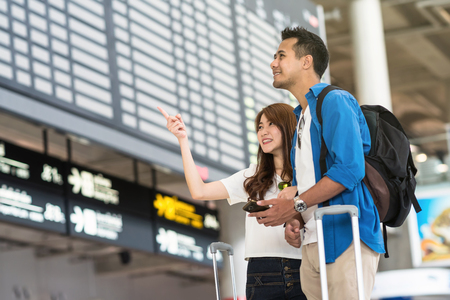 Asian couple traveler holding the smart mobile phone and pointing at the flight information screen in modern an airport, travel and transportation with technology concept.