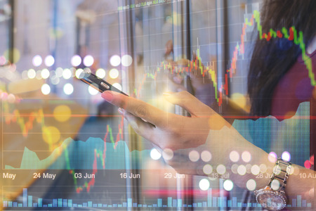 stockmarket: Double exposure of Closeup woman using the smart mobile phone over the soft screen of stock market background, business trading concept