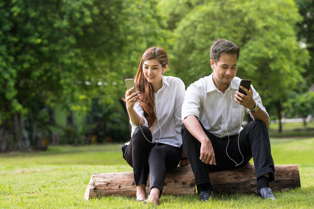 Happy asian couple using and listening the song via smart phone camera in the park, lover and lifestyle concept