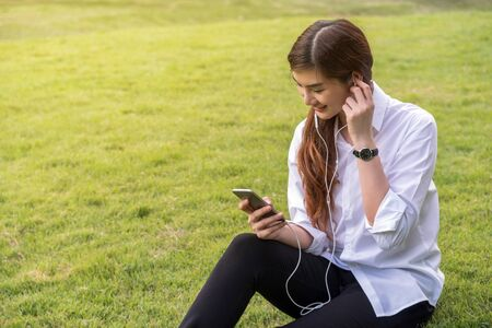 Happy asian Beautiful young woman listening the song via smart phone camera in the park,  lifestyle concept Stock Photo